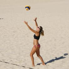 Fit lady playing beach volleyball