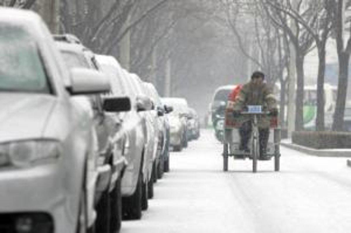 Pouličný predajca v zasneženom Pekingu.