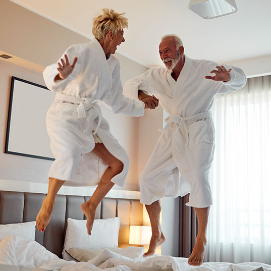 Affluent couple jumping on a hotel bed