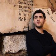 """Portrait devant un mur taggé de l'artiste Sol pour la promotion de """"Vers le Nord"""""""