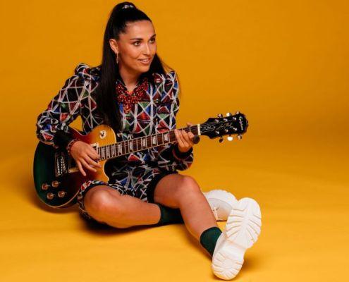 portrait de l'artiste française Camille Esteban et sa guitare sur fond orange