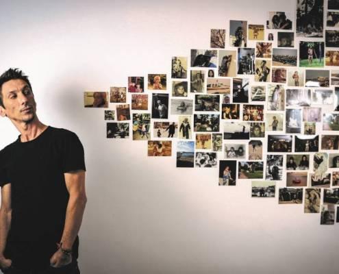 Thomas Cousin regardant des photos au mur pour la sortie de son premier album solo