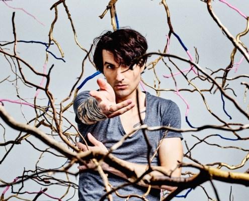 portrait de Louis Arlette tendant la main dans des branchages