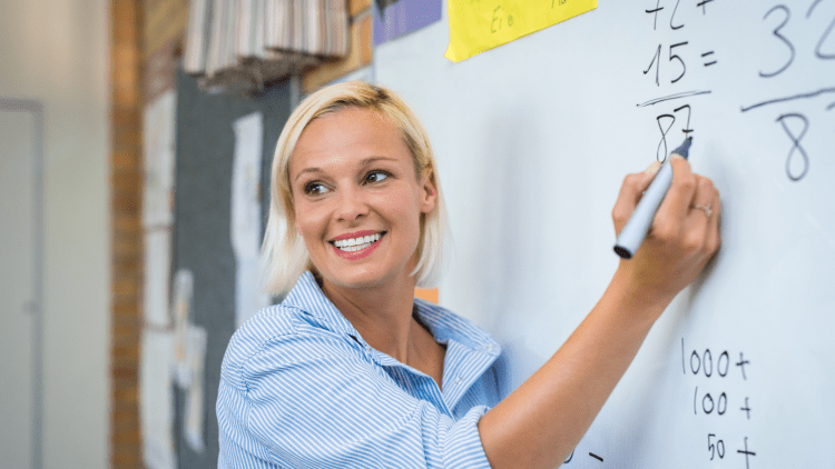 A smiling young white woman writes addition problems on a white board