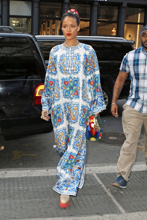 These flowy maxi dresses are quickly becoming a summer staple for Rihanna. The singer styled the look for an evening out by pairing this tile-print Dolce & Gabbana caftan with a colorful clutch, also by Dolce & Gabbana, plus Stella McCartney platforms and a whimsical flower hair accessories.