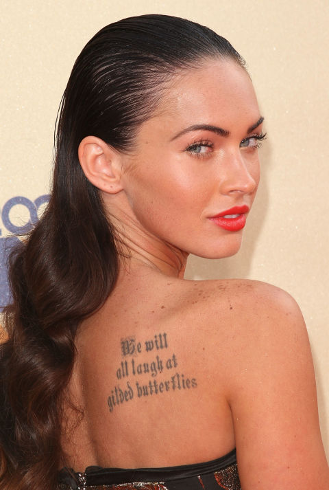 """The Transformers star has been inked and de-inked a couple times before (she got rid of her Marilyn Monroe tattoo to avoid """"attracting negative energy"""") but the most prominent is the script on her back that adapts a line from Shakespeare's King Lear. It reads, """"We will all laugh at gilded butterflies"""" and she has been quoted saying that it's a reminder """"to not get too caught up in Hollywood because people will end up laughing at you."""""""