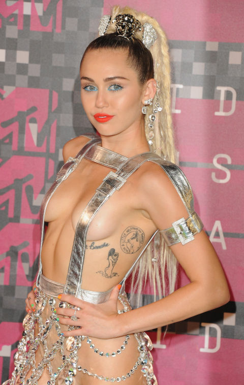 """Miley Cyrus got her first tattoo at 17—script of """"Just Breathe"""" below her breast—as a tribute to her friend Vanessa who had died of lung disease and both of her grandfathers, who had died of lung cancer.""""It reminds me not to take things for granted. I mean breathing—that was something none of them could do, the most basic thing. And I put it near my heart, because that is where they will always be,"""" she told Harper's Bazaar."""