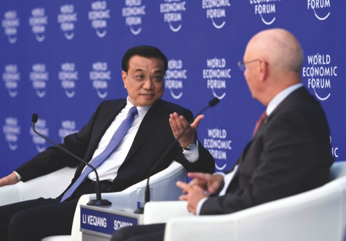 Chinese Premier Li Keqiang, left, talks with Klaus Schwab, founder and executive chairman of the World Economic Forum, during a meeting ahead of the Summer Davos forum in Tianjing, northern China