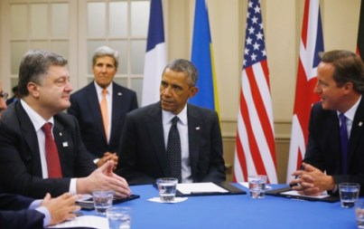U.S. President Barack Obama, center, is seated at a table with Ukraine President Petro Poroshenko, left, and British Prime Minister David Cameron as they meet about Ukraine at the NATO summit at Celtic Manor in Newport, Wales