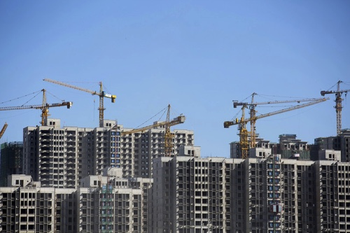 Cranes operate at a residential construction site in Beijing