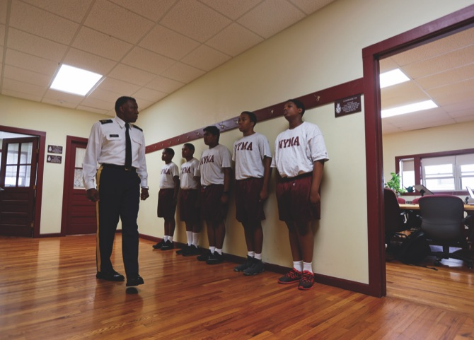 Master Sgt. Fletcher Bailey inspects cadets before a junior ROTC class