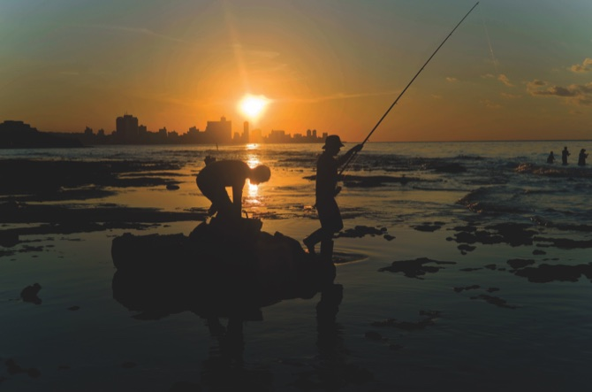 Fishermen throw their fishing rods from Chivo beach as the sun sets in Havana