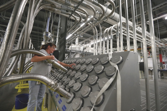 A worker moves a tube to sort recycled plastic bottle chips being processed at the Repreve Bottle Processing Center