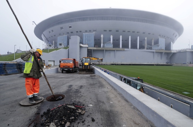 A worker cleans sewers near the retractable football pitch at the soccer stadium, which is under construction on Krestovsky Island, in St. Petersburg