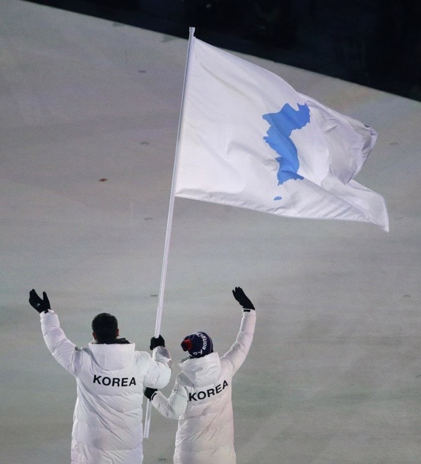 A torchbearer lights the Olympic flame during the opening ceremony of the 2018 Winter Olympics