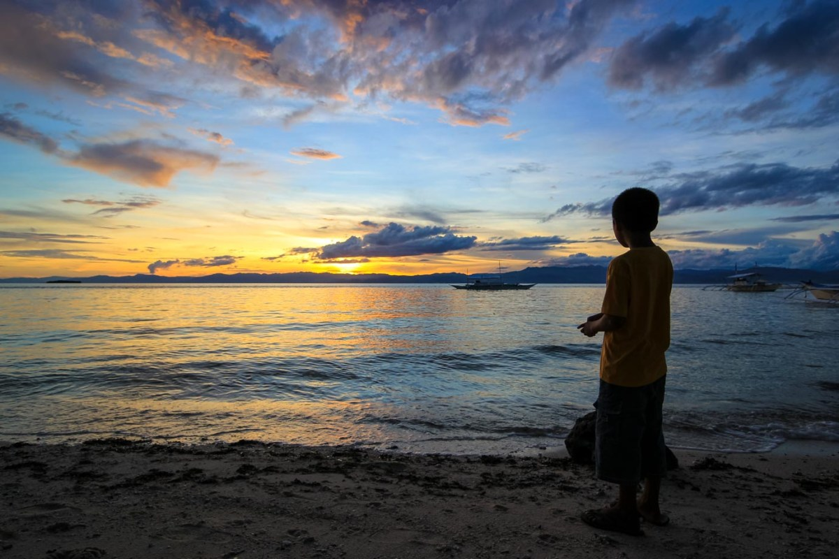 A kid watching the sun set in the Philippines