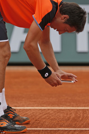 Ukraine's Sergiy Stakhovsky takes a picture with his Apple iPhone after contesting the decision of the umpire. (Photo: AP)