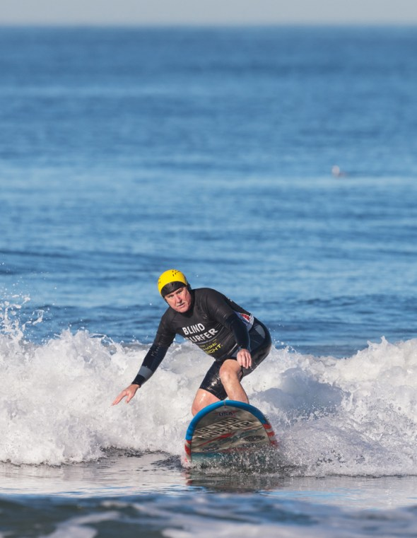 """Leason wears a rash guard with """"Blind Surfer"""" printed on the front to signal to fellow surfers he needs some room."""