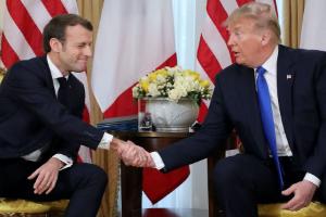 UK tech tax: Donald Trump and Emmanuel Macron shake hands