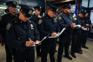 NYPD iPhone app: Officers filling out memo books at a recent roll call at the 90th Precinct Station House in Williamsburg, Brooklyn. Photo: Chang W. Lee/The New York Times