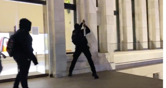 Apple Stores looted. A looter dressed in black uses a bat to break window glass in order to gain access to Apple Carnegie Library in Washington, D.C.