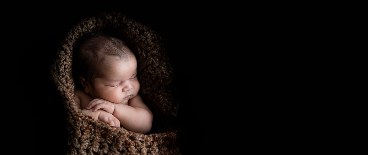 Swaddled baby with black background