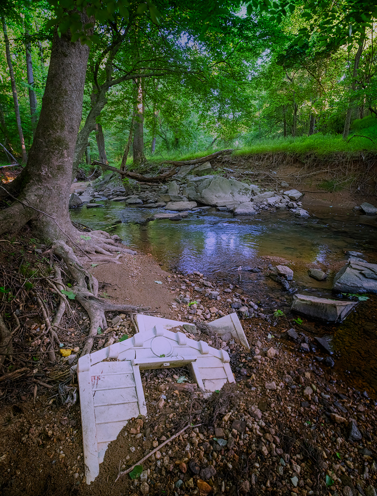 Suburban stormwater runoff washes chemicals and trash into our streams, including this half buried child's playhouse