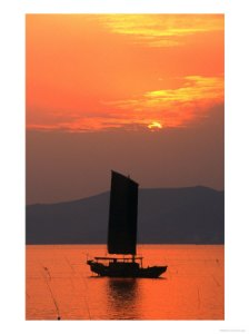 A boat sailing away in sunset