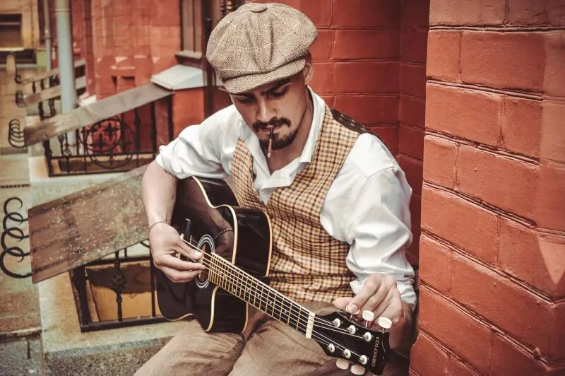 帽子を被りギターを弾く男性