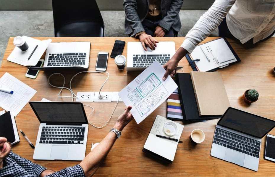 Na imagem 3 pessoas em uma mesa, 2 delas estão passando papel de uma para outra