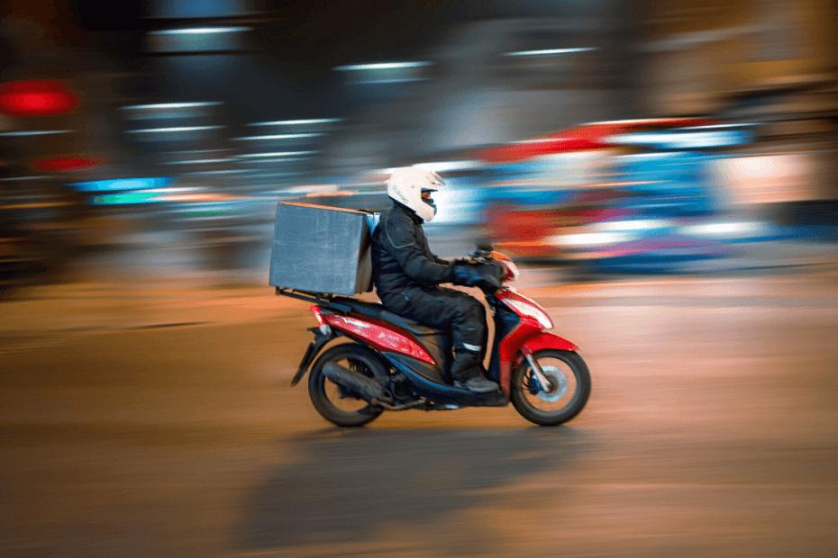 Motoboy em uma moto vermelha trabalhando a noite