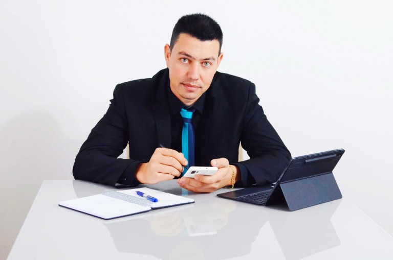 Angelo, co-fundador do aplicativo de transporte Chofer 46, sentado com um celular, tablet, caderno e canetas.