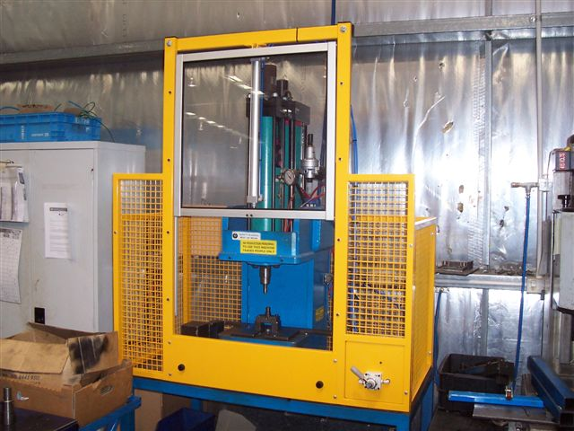 Vertically sliding power-operated guard door on the front of a small hydraulic press.