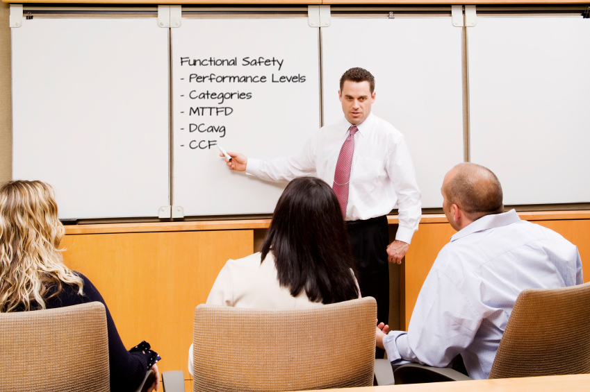 Man training a group of people, pointing to Functional Safety topics on the whiteboard