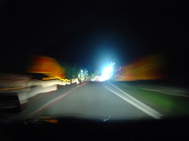 Bright lights flare at the end of a motorway at night