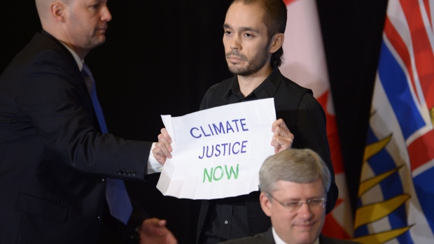 "Sean Devlin, a climate change protester, holds a sign reading ""Climate justice now"" during an event with Prime Minister Stephen Harper at the Vancouver Board of Trade on Monday Jan. 6, 2013. (Jonathan Hayward/Canadian Press)"