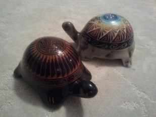 Black clay turtle in foreground (by Johnny Williams); in background, a white-grey pottery turtle with rainbow-painted etched shell (Tom Vail Jr.).