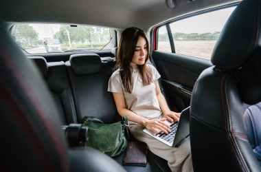 woman using laptop computer inside vehicle