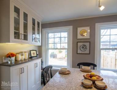 Compact Kitchen Design with Quartz Counters, Glass Inserts in Shaker Style Cabinets and Dry Bar