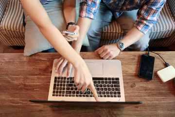 Casal mexendo num MacBook