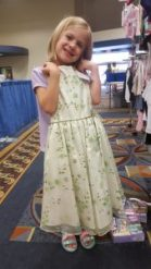 Isobel models a little girl's dress, for sale at Second Impressions.