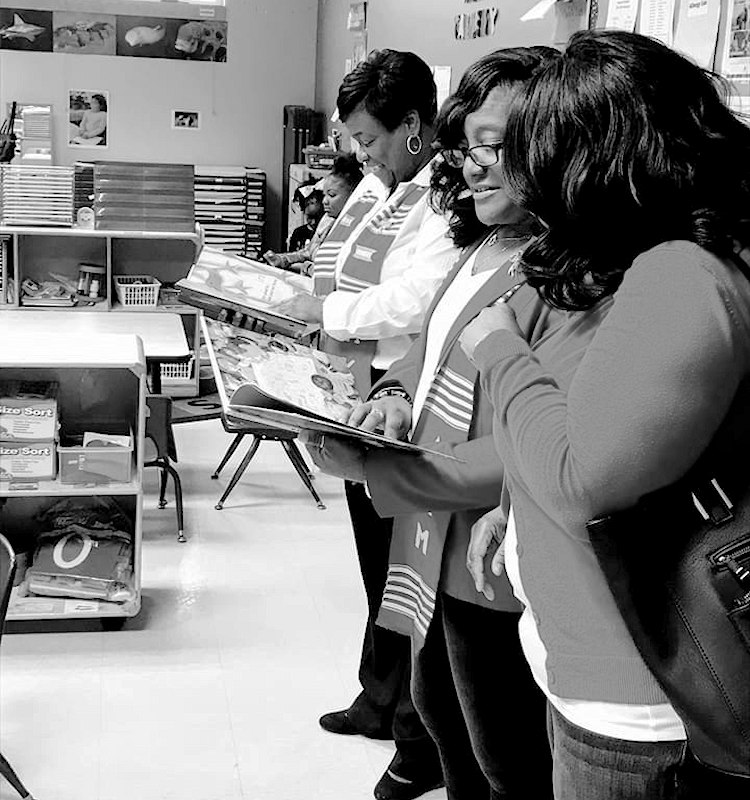 Lamda Kappa Mu sorors reading to children for Christmas book drive