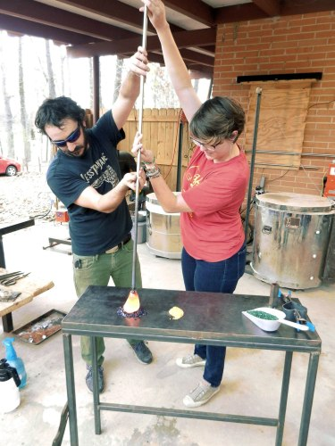 Helping a student shape glass object