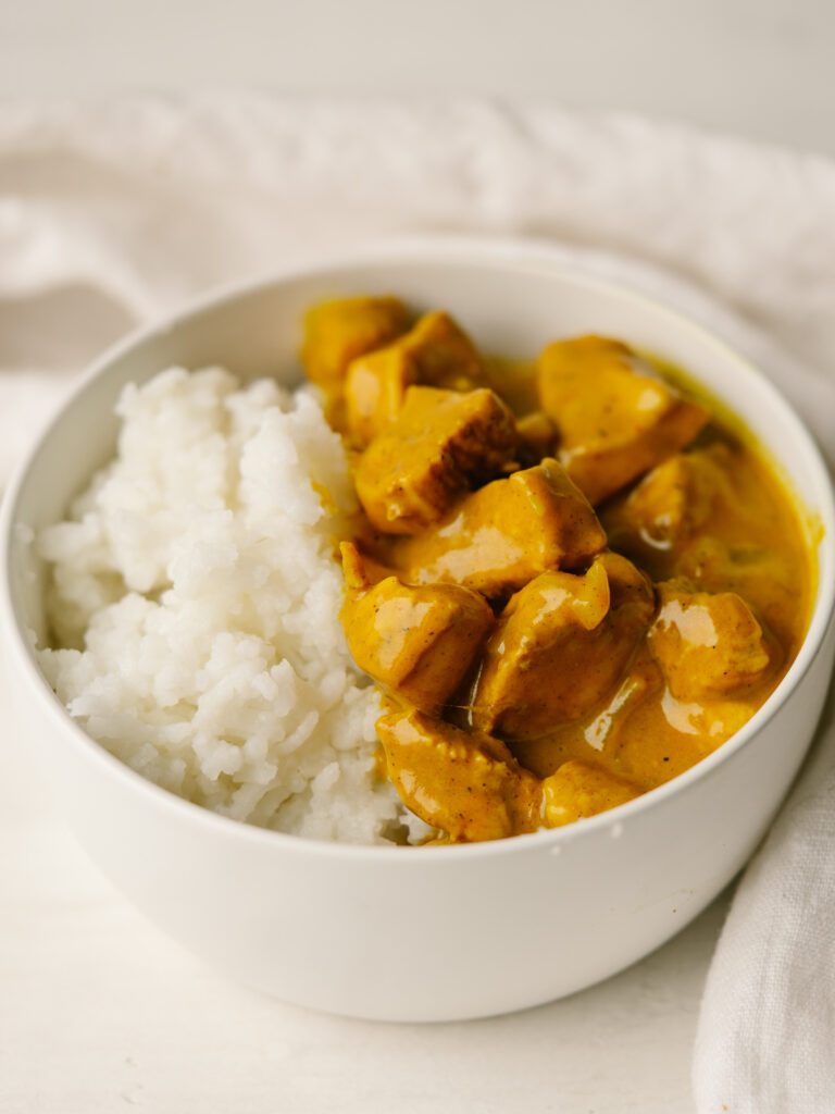 Three quarter view of pumpkin coconut chicken curry in a bowl with white rice