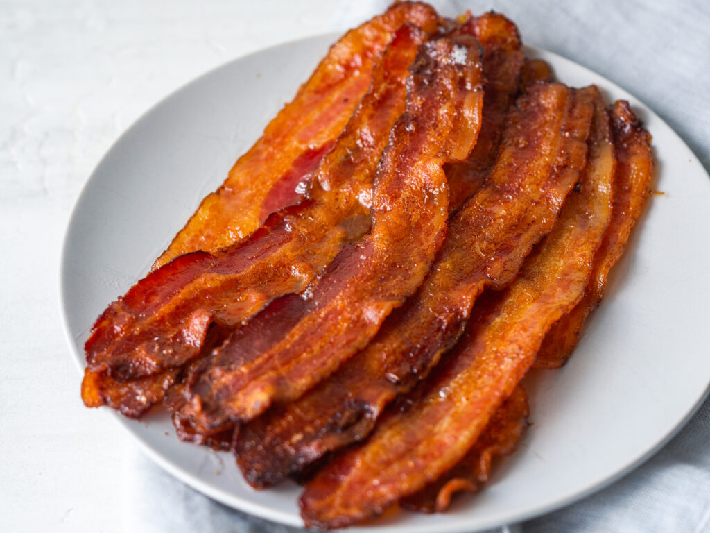 Three quarter view of crispy bacon slices on a plate