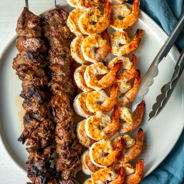 Above view of grilled surf and turf skewers on a plate with tongs