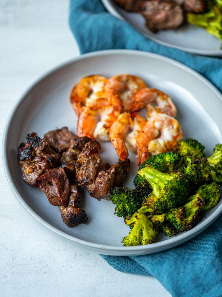 Marinated grilled steak and shrimp served with grilled broccoli