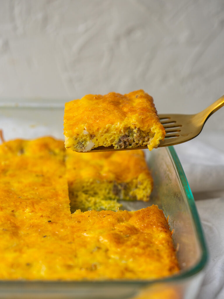 side view of a slice of cheeseburger breakfast casserole being pulled out of the pan