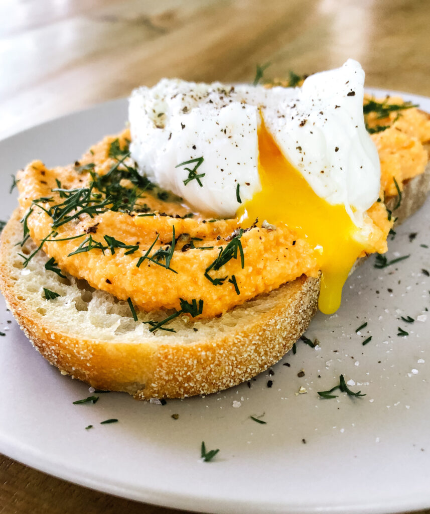 Toast with buffalo dip on top and an egg on top with yolk dripping