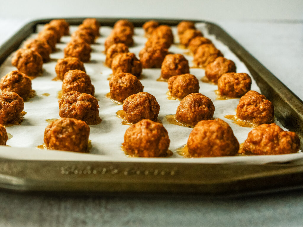 Side view of a sheet pan of baked mini beef meatballs for Italian meatball soup